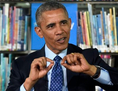 """President Barack Obama speaks at Anacostia Library in Washington, Thursday, April 30, 2015, as he participates in a live """"virtual field trip"""" with middle school students to announce two initiatives to improve education through digital connectivity. The president announced Thursday that major book publishers will provide more than $250 million in free e-books to low-income students and that he is seeking commitments from local governments and schools nationwide to provide library cards to all students.  (AP Photo/Susan Walsh)"""