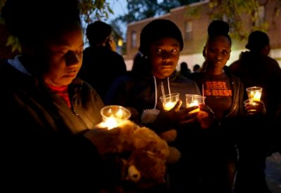 In this Oct. 9, 2014 file photo, people gather for a candlelight vigil to remember Vonderrit Myers Jr., in St. Louis. An attorney for the family of the black 18-year-old shot and killed last October by an off-duty, white St. Louis police officer said Tuesday, May 19, 2015 he plans to file a wrongful-death lawsuit, after a prosecutor said the officer would not face criminal charges. (AP Photo/Jeff Roberson, File)
