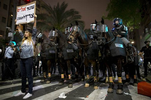 """An Israeli protester holds a sign in Hebrew reading """"violent policeman should be sentenced""""  during clashes between Israel's, mainly Jewish Ethiopians and Israeli riot police during a protest against racism and police brutality in Tel Aviv, Israel, Sunday, May 3, 2015, as several thousand people from Israel's Jewish Ethiopian minority protest, shutting down a major highway and clashing with police on horseback long into the night. The protest was mostly peaceful during the day, but by nightfall became violent with at least 20 officers were hurt and """"multiple protesters"""" arrested, Police Spokesman Micky Rosenfeld said. (AP Photo/Oded Balilty)"""