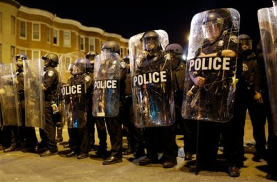 In this April 28, 2015 file photo, police stand in formation as a curfew approache in Baltimore, a day after unrest that occurred following Freddie Gray's funeral.  The prevailing images of protests in Baltimore and Ferguson, Missouri, over police killings of black men were of police in riot gear, handcuffed protesters, tear gas and mass arrests. The main images of a fatal gun battle between armed bikers and police in Waco, Texas, also showed mass arrests _ carried out by nonchalant-looking officers sitting around calm bikers on cell phones. (AP Photo/Patrick Semansky, File)