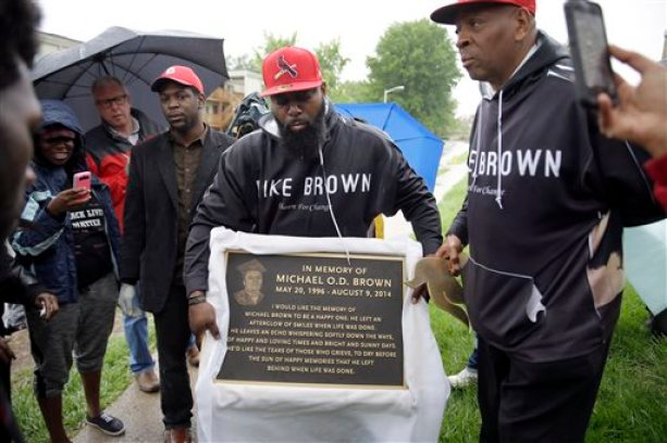 Michael Brown Sr. holds up a plaque remembering his son, Michael Brown, to show volunteers as they remove items left at a makeshift memorial to Michael Brown Wednesday, May 20, 2015, in Ferguson, Mo. The memorial that has marked the place where Brown was fatally shot by a police officer in August has been removed and will be replaced with the permanent plaque. (AP Photo/Jeff Roberson)