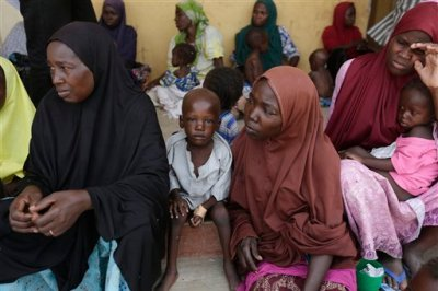 Women and children rescued by Nigerian soldiers from Boko Haram extremists at Sambisa Forest wait for treatment at at a refugee camp in Yola, Nigeria Monday, May 4, 2015. Even with the crackle of gunfire signaling rescuers were near, the horrors did not end: Boko Haram fighters stoned captives to death, some girls and women were crushed by an armored car and three died when a land mine exploded as they walked to freedom. (AP Photo/Sunday Alamba)