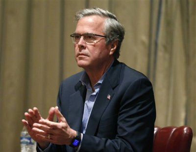 In this April 7, 2015, file photo, former Florida governor and potential Republican presidential candidate Jeb Bush applauds a speaker during an energy forum which he hosted, at the Brown Palace Hotel in Denver. To judge them solely by their travels over the past month, you might think Bush has already plunged into the general election and Hillary Rodham Clinton has a serious fight on her hands for the Democratic nomination. (AP Photo/Brennan Linsley, File)