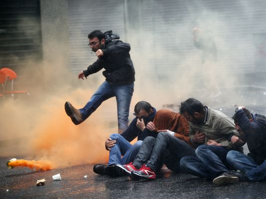 A demonstrator kicks a smoke canister as others try to protect themselves from the effects of tear gas, fired by riot police officers during clashes in Istanbul, Turkey, on May 1, 2015. (Photo: Emrah Gurel, AP)