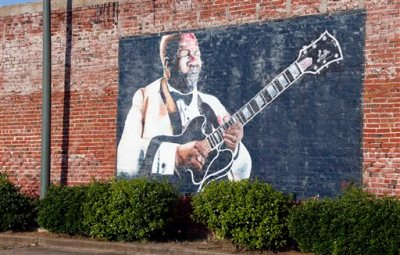 """In this photo taken May 6, 2015, a wall mural of B.B. King overlooks a downtown parking area in Indianola, Miss. King claimed Indianola as his hometown after moving there as a teenager. The influence of the acclaimed """"King of the Blues,"""" is seen throughout the small Mississippi Delta town. King died Thursday night, May 14, 2015, at age 89 in Las Vegas, where he had been in hospice care. (AP Photo/Rogelio V. Solis)"""