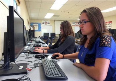 In this April 30, 2015 photo, Leticia Fonseca, 16, left, and her twin sister, Sylvia Fonseca, right, work in the computer lab at Cuyama Valley High School after taking the new Common Core-aligned standardized tests in New Cuyama, Calif. The Cuyama Joint Unified School District is 60 miles from the nearest city and has Internet connections about one-tenth the minimum speed recommended for the modern U.S. classroom. Across the country, school districts in rural areas and other pockets with low bandwidth are confronting a difficult task of administering new Common Core-aligned standardized tests to students online. (AP Photo/Christine Armario)