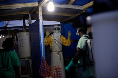 In this Thursday Nov. 20, 2014 file photo, an MSF Ebola heath worker is sprayed as he leaves the contaminated zone at the Ebola treatment centre in Gueckedou, Guinea. Authorities in the country where the Ebola epidemic began are concerned about a new outbreak of cases just as officials hoped the crisis was coming under control. (AP Photo/Jerome Delay, File)