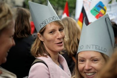 """Teachers and education employees wear hats reading """"pseudo intellectual"""" during a demonstration to protest government plans to reform the education system, in Paris, France, Tuesday, May 19, 2015. France is proposing education reforms that would end elite bilingual programs and give schools more say in how students spend their time, a move to fight the inequality in education that threatens the country's future. (AP Photo/Francois Mori)"""
