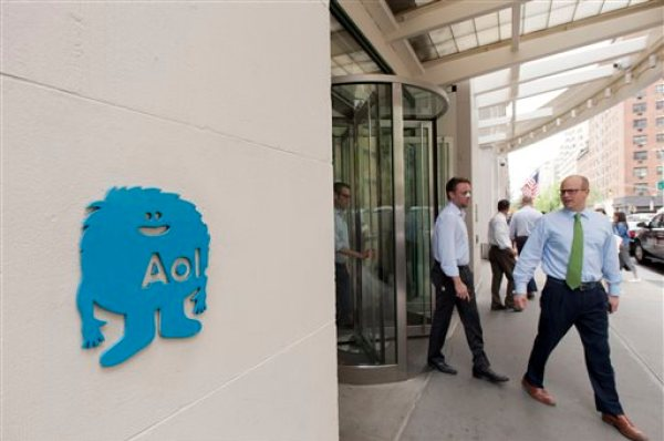 People walk out of the New York office building where AOL headquarters is located, Tuesday, May 12, 2015. Verizon is buying AOL for about $4.4 billion, advancing the telecom's push in both mobile and advertising fields. (AP Photo/Mark Lennihan)