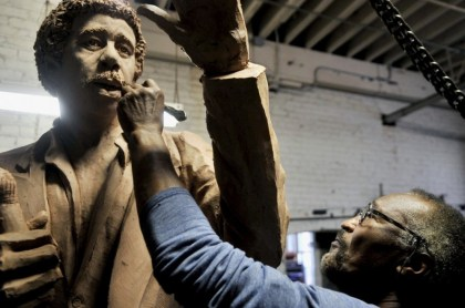 Artist Preston Jackson uses a butter knife to work on the small details of his oil-based, clay model statue of comedian Richard Pryor at his studio in the Contemporary Art Center building in Peoria, Ill. (Nick Schnelle/Journal Star via AP)