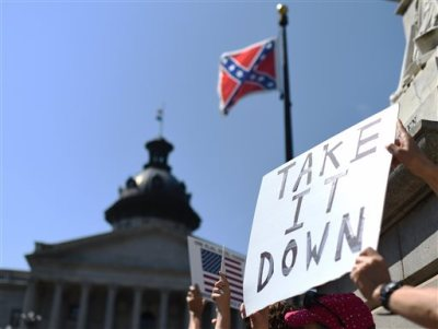 Protesters hold a sign during a rally to take down the Confederate flag at the South Carolina Statehouse, Tuesday, June 23, 2015, in Columbia, S.C. For years, South Carolina lawmakers refused to revisit the Confederate flag on Statehouse grounds, saying the law that took it off the dome was a bipartisan compromise, and renewing the debate would unnecessarily expose divisive wounds. The shooting deaths of nine people at a black church in Charleston, S.C., have reignited calls for the Confederate flag flying on the grounds of the Statehouse in Columbia to come down. (AP Photo/Rainier Ehrhardt)