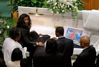 """In this April 27, 2015, file photo, Gloria Darden, mother of Freddie Gray, is comforted as she embraces his body before his funeral at New Shiloh Baptist Church in Baltimore. A medical examiner found Freddie Gray suffered a """"high-energy injury,"""" most likely caused when the Baltimore police van he was riding in braked sharply, according to an autopsy report obtained by The Baltimore Sun. (AP Photo/Patrick Semansky, File)"""