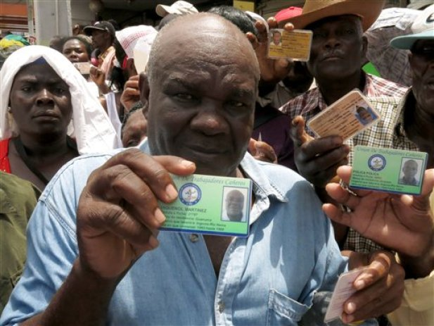 Haitian Jaquenol Martinez shows a card that proves that he has worked in the Dominican sugar cane fields since 1963, while trying to apply for a temporary resident permit, in Santo Domingo, Dominican Republic, Monday, June 15, 2015. Hundreds of Haitians are waiting in long lines throughout the Dominican Republic trying to secure legal residency as they face the threat of deportation. The government has given non-citizens until Tuesday to register under an initiative aimed at regulating the flow of migrants from neighboring Haiti. (AP Photo/Ezequiel Abiu Lopez)