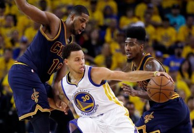 Golden State Warriors guard Stephen Curry (30) tries to control the ball as he is guarded by Cleveland Cavaliers center Tristan Thompson (13) and guard Iman Shumpert during the first half of Game 2 of basketball's NBA Finals in Oakland, Calif., Sunday, June 7, 2015. (AP Photo/Ben Margot)