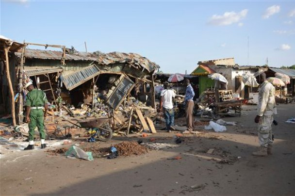 People gather at the site of a suicide bomb attack at a market in Maiduguri, Nigeria, Monday June 22, 2015. Two girls blew themselves up on Monday near a crowded mosque in northeast Nigeria's biggest city, killing about 30 people, witnesses said. It is the fourth suicide bombing this month in Maiduguri, which is the birthplace of the Boko Haram Islamic extremist group. (AP Photo/Jossy Ola)