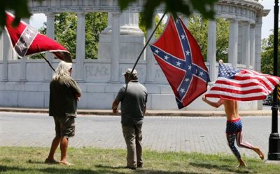 "Members of the Virginia Flaggers demonstrate near the monument for Confederacy President Jefferson Davis as a runner carries an American flag, Thursday, June 25, 2015, on Monument Avenue in Richmond, Va. The monument was vandalized overnight, spray-painted with the phrase ""Black Lives Matter."" The vandalism comes after a shooting in Charleston, S.C. sparked a nationwide debate on the public display of Confederate imagery. (AP Photo/Steve Helber)"