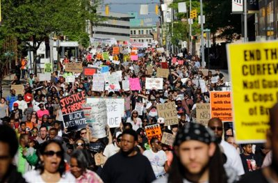"""In this May 2, 2015 file photo, protesters march through Baltimore the day after charges were announced against the police officers involved in Freddie Gray's death. A medical examiner found Freddie Gray suffered a """"high-energy injury,"""" most likely caused when the Baltimore police van he was riding in braked sharply, according to an autopsy report obtained by The Baltimore Sun. (AP Photo/Patrick Semansky, File)"""