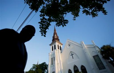 Emanuel AME Church stands in the background as a mourner visits a sidewalk memorial in memory of the shooting victims Saturday, June 20, 2015, in Charleston, S.C. (AP Photo/David Goldman)