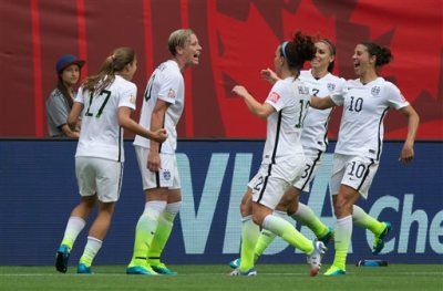 United States' Tobin Heath, Abby Wambach, Lauren Holiday, Christie Rampone and Carli Lloyd, fromleft, celebrate Wambach's goal against Nigeria during the first half of a FIFA Women's World Cup soccer game Tuesday, June 16, 2105, in Vancouver, British Columbia, Canada. (Darryl Dyck/The Canadian Press via AP)