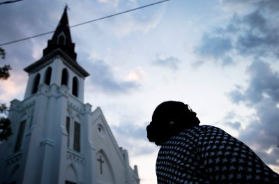 Doris Simmons, of Charleston, S.C. stands next to Emanuel AME Church, the scene of last week's mass shooting, as the sun rises Friday, June 26, 2015, in Charleston.  President Barack Obama delivered the eulogy for one of the victims, Sen. Clementa Pinckney, during his funeral Friday at a nearby college arena. (AP Photo/David Goldman)