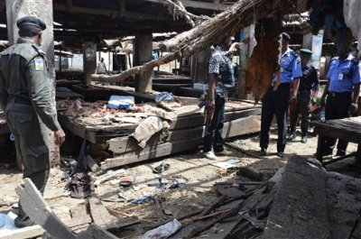Police officers inspect the site of  a suicide bomb attack at a market in Maiduguri , Nigeria, Tuesday, June 2, 2015.  Boko Haram attacked the northeastern Nigerian city of Maiduguri on Tuesday with deafening explosions from the west and a suicide bombing near the center that witnesses said killed as many as 20 people. (AP Photo/Jossy Ola)
