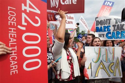 """Jessica Ellis, right, with """"yay 4 ACA"""" sign, and other supporters of the Affordable Care Act, react with cheers as the opinion for health care is reported outside of the Supreme Court in Washington,Thursday June 25, 2015. The Supreme Court on Thursday upheld the nationwide tax subsidies under President Barack Obama's health care overhaul, in a ruling that preserves health insurance for millions of Americans.  (AP Photo/Jacquelyn Martin)"""