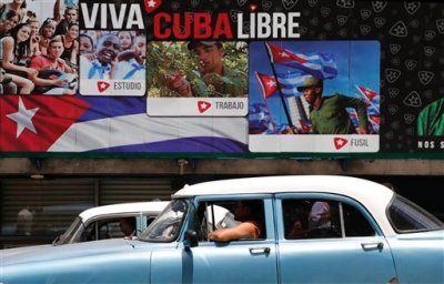 "A classic American car passes in front of some signs that reads in Spanish ""Long Live Free Cuba"" in Havana, Cuba, Tuesday, June 16, 2015. Six months ago Wednesday, Presidents Barack Obama and Raul Castro stunned the world by announcing an end to their nations' half-century of official hostility. In Cuba, aging leaders fear swift, uncontrolled change that would cost them power and spawn disorder in a country that dreads the violence and inequality scarring its neighbors. That fear is heightened by the United States' long history of trying to topple Castro and his brother Fidel. (AP Photo/Desmond Boylan)"