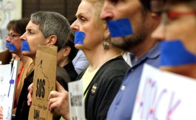 In this June 4, 2015, photo, University of Wisconsin of  Milwaukee associate professor Lorraine Malcoe, second from left, joins other angry educators and supporters in protest by taping their mouths shut outside a Board of Regents meeting in Milwaukee. A spokesman for university professors says Gov. Scott Walker's education policy changes that eliminate tenure could embolden faculty in Wisconsin and around the country to become more organized as Walker mounts his expected run for the White House. (Mike De Sisti/Milwaukee Journal Sentinel via AP)