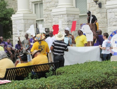 Rally in front of Shelby County courthouse participants holding up signs of states covered by the Voting Rights Act. (Courtesy Photo)