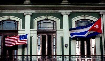 FILE - In this Jan. 19, 2015 file photo, a Cuban and American flag wave from the balcony of the Hotel Saratoga in Havana. President Barack Obama will announce July 1 that the U.S. and Cuba have reached an agreement to open embassies in Havana and Washington, a senior administration official said. (AP Photo/Ramon Espinosa, File)