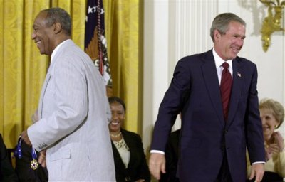 In this July 9, 2002 file photo, President George W. Bush lets out a laugh after failing to get the clasp together on Bill Cosby's Presidential Medal of Freedom, which he holds, after Bush tried to put on the entertainer, in the East Room of the White House in Washington. President Barack Obama is rejecting the idea of revoking Cosby's Presidential Medal of Freedom because of sexual misconduct allegations. Obama says there's no precedent or mechanism to take back the medal. He declined to talk about the specific allegations against Cosby because there are pending legal matters. (AP Photo/Kenneth Lambert, File)
