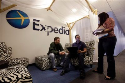 In this Tuesday, Jan. 15, 2013, file photo, Expedia analytics team workers Mike Brown, left, Saurin Pandya and Prashanti Tata chat in an alcove set up for employees, in Bellevue, Wash. The American Hotel & Lodging Association on Thursday, Aug. 6, 2015 issued a statement announcing its opposition to the proposed combination of travel booking sites Expedia and Orbitz, saying that the deal would mean higher prices for vacationers and larger fees for hotel owners. (AP Photo/Elaine Thompson, File)