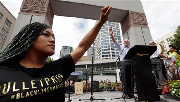 Mara Jacqueline Willaford, left, holds her fist overhead as Democratic presidential candidate Sen. Bernie Sanders, I-Vt., waves to greet the crowd before speaking at a rally Saturday, Aug. 8, 2015, in downtown Seattle. Willaford and another co-founder of the Seattle chapter of Black Lives Matter took over the microphone just after Sanders began to speak and refused to relinquish it. Sanders eventually left the stage without speaking further and instead waded into the crowd to greet supporters. (AP Photo/Elaine Thompson)