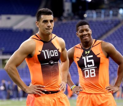 In this Feb. 21, 2015, file photo, then-Oregon quarterback Marcus Mariota (11) and then-Florida State quarterback Jameis Winston (15) wait to run a drill at the NFL football scouting combine in Indianapolis. It's time for Winston and Mariota to show what they've been learning at training camp in their preseason debuts. (AP Photo/David J. Phillip, File)