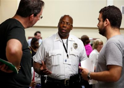 In this July 28, 2015, file photo, interim police Chief Andre Anderson, center, talks with activists John Powell, left, and Marc DeSantis at the end of a city council meeting in Ferguson, Mo. Anderson says he wants his officers engaging with the community, getting out of their cars and mingling with people in an effort to build better relations. As Ferguson protests fade, activists and the suburb are looking ahead. (AP Photo/Jeff Roberson, File)