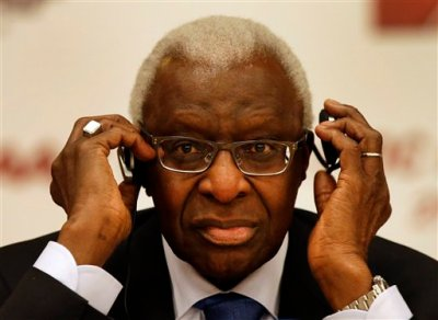 IAAF president Lamine Diack adjusts his headphones during a joint IOC and IAAF press conference on the side of the World Athletic Championships in Beijing, Friday, Aug. 21, 2015. (AP Photo/Kin Cheung)