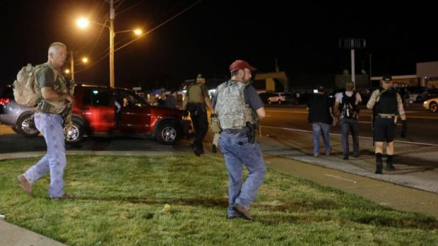 "Heavily armed civilians with a group known as the Oath Keepers arrive in Ferguson, Mo., early Tuesday, Aug. 11, 2015. The far-right anti-government activists, largely consists of past and present members of the military, first responders and police officers. St. Louis County Police Chief Jon Belmar said the overnight presence of the militia group, wearing camouflage bulletproof vests and openly carrying rifles and pistols on West Florissant Avenue, the hub of marches and protests for the past several days, was ""both unnecessary and inflammatory."" (AP Photo/Jeff Roberson)"
