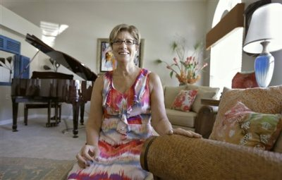 In this Aug. 10, 2015 photo, Debbie Cooley-Guy sits in the living room of her new home in New Port Richey, Fla. Seven years after the real estate bust, many of those who lost their homes, including Cooley-Guy, have rebuilt their credit and are back in the market. Experts say these boomerang buyers will be hugely influential in the real estate market in the coming year. (AP Photo/Chris O'Meara)