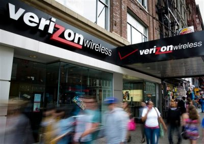 In this June 6, 2013, file photo, pedestrians pass a Verizon Wireless store on Canal Street in New York. Verizon, the nation's largest wireless provider, said it will stop requiring two-year service contracts, but customers will no longer be able to buy phones at discounted prices of $100 or $200. The new plans take effect Aug. 13. (AP Photo/John Minchillo, File)
