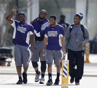 In this April 25, 2014, file photo, unidentified Northwestern football players walk between their locker room and McGaw Hall, where voting is taking place on the student athlete union question, in Evanston, Ill. The National Labor Relations Board has dismissed a historic ruling that Northwestern University football players are school employees who are entitled to form what would be the nation's first union of college athletes. The NLRB released its decision Monday, Aug. 17, 2015. The losing side does not have an option to appeal. (AP Photo/Charles Rex Arbogast, File)