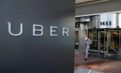 In this photo taken Tuesday, Dec. 16, 2014, a man leaves the headquarters of Uber in San Francisco. A federal judge granted class-action status Tuesday, Sept. 1, 2015, to a lawsuit in California against Uber over the payment of its drivers, upping the stakes for the ride-hailing company in the case. (AP Photo/Eric Risberg, File)