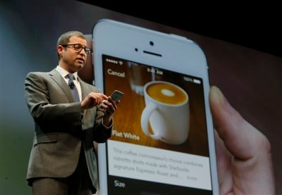 In this March 18, 2015 file photo, Adam Brotman, Starbucks chief digital officer, talks about the company's new mobile ordering app at Starbucks Coffee Company's annual shareholders meeting in Seattle. The Seattle-based coffee chain says its mobile app that lets people order and pay in advance will be available nationally starting Tuesday, Sept. 22, 2015. (AP Photo/Ted S. Warren, File)