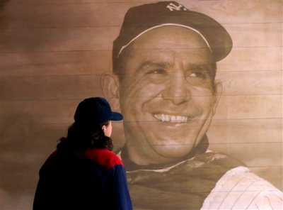 T.J. Hitchings, of Plainsboro, N.J., looks at a portrait of former New York Yankees hall of fame catcher Yogi Berra at the Yogi Berra Museum, Wednesday, Sept. 23, 2015, in Little Falls, N.J. Berra died Tuesday at the age of 90. (AP Photo/Julio Cortez)