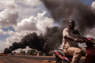 "Tires burn, left rear,  as people continue  protesting against the recent coup in  Ouagadougou,  Burkina Faso, Saturday, Sept. 19, 2015.  Senegal President Macky Sall deplored a ""lack of dialogue"" as mediators entered a second day of talks on Saturday over Burkina Faso's coup in which an elite military unit overthrew the transitional government. (AP Photo/Theo Renaut)"