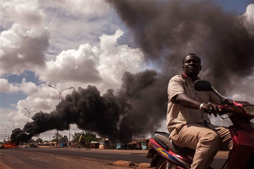 """Tires burn, left rear,  as people continue  protesting against the recent coup in  Ouagadougou,  Burkina Faso, Saturday, Sept. 19, 2015.  Senegal President Macky Sall deplored a """"lack of dialogue"""" as mediators entered a second day of talks on Saturday over Burkina Faso's coup in which an elite military unit overthrew the transitional government. (AP Photo/Theo Renaut)"""