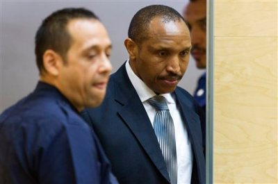 Bosco Ntaganda, center right, a Congo militia leader known as The Terminator, enters the court room for the start of his trial at the International Criminal Court on charges including murder, rape and sexual slavery allegedly committed in the eastern Ituri region of Congo from 2002-2003, in The Hague, Netherlands, Wednesday, Sept. 2, 2015. (Michael Kooren/Pool Photo via AP)