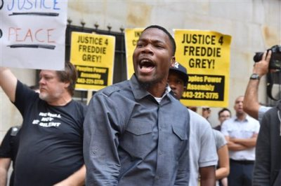 "Protesters gather outside Baltimore Circuit Court, as the first court hearing was set to begin in the case of six police officers criminally charged in the death of Freddie Gray, on Wednesday, Sept. 2, 2015 in Baltimore.  Six police officers face charges that range from second-degree assault, a misdemeanor, to second-degree ""depraved-heart"" murder. (Kim Hairston/The Baltimore Sun via AP)"