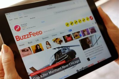 The BuzzFeed website is displayed on an iPad held by an Associated Press staffer in Los Angeles, on Tuesday, Sept. 1, 2015. Comcast, which became a TV powerhouse by signing up Generation Xers, is investing in online media outlets like BuzzFeed and Vox that attract millenial viewers. (AP Photo/Richard Vogel)