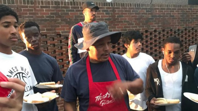 Coach Ken Roberts (center) and members of the Northwestern junior varsity and varsity football teams, gathered at the University Park Church of Christ for a cookout.