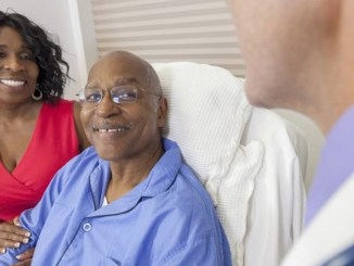 Happy senior African American man patient recovering in hospital bed with male doctor and wife